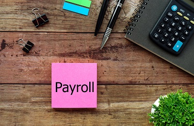 sticky note on table that reads 'payroll'